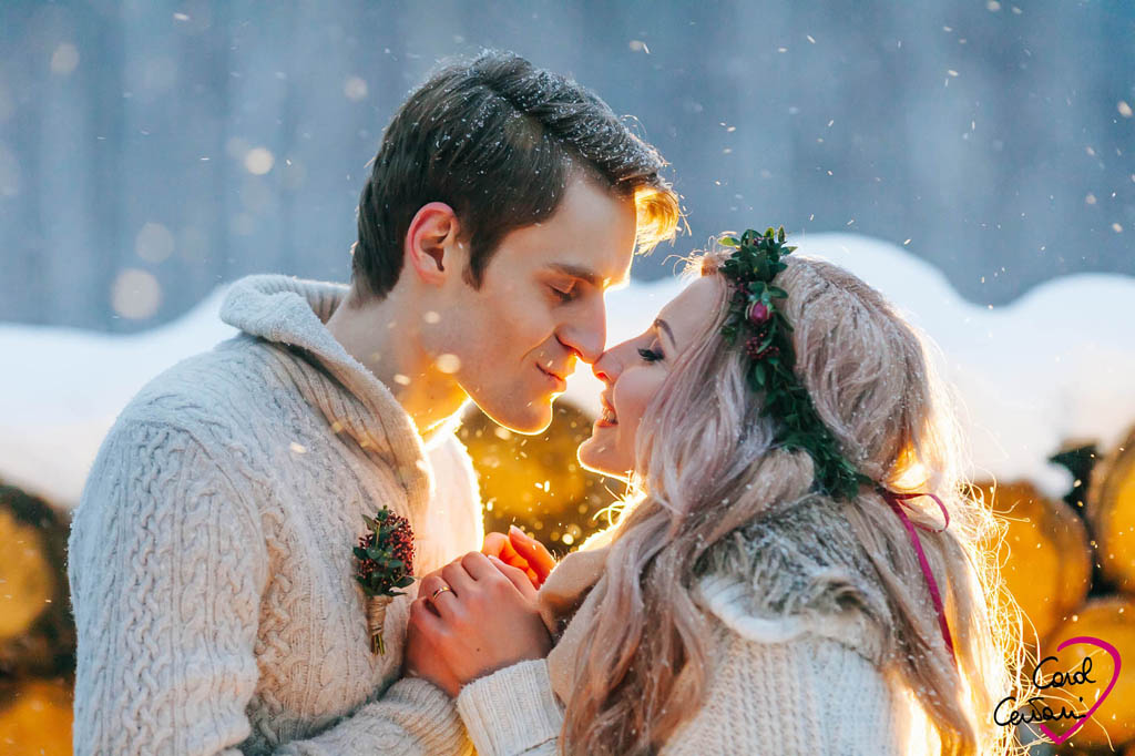 Groom and bride marry outdoors under a gentle snowfall