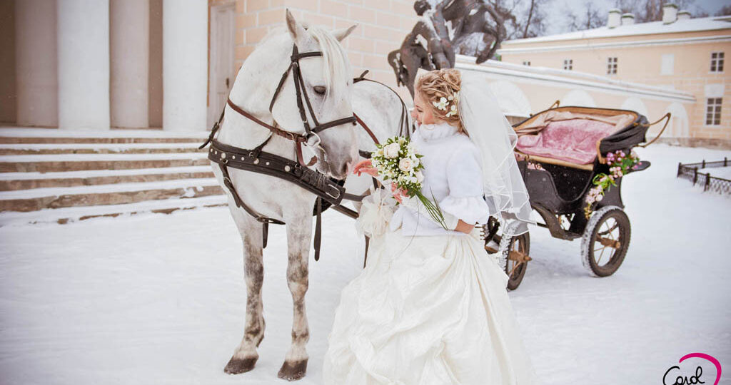 The beautiful bride with a horse in front of a church. Planning of weddings, Snow Winter Weddings