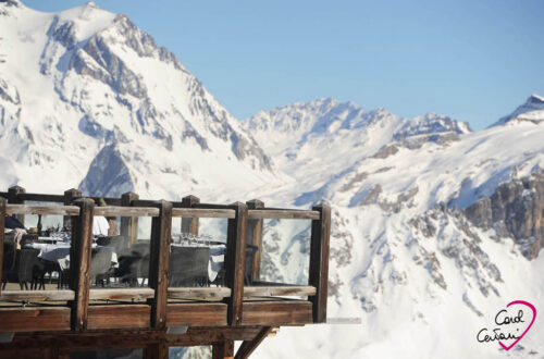 Terrace of a restaurant in a winter ski resort with snowy mountains